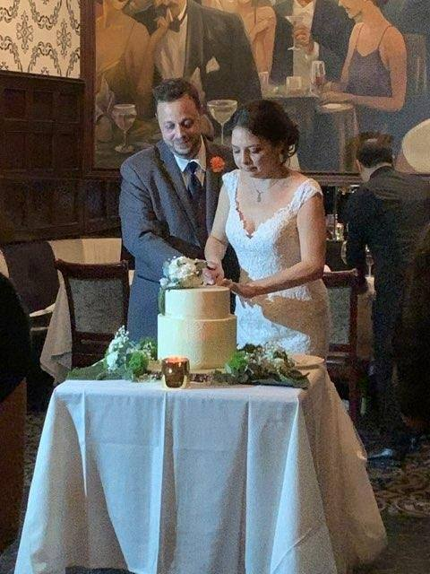 new married couple at wedding cutting cake
